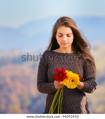Sad young woman with flowers outdoor portrait.