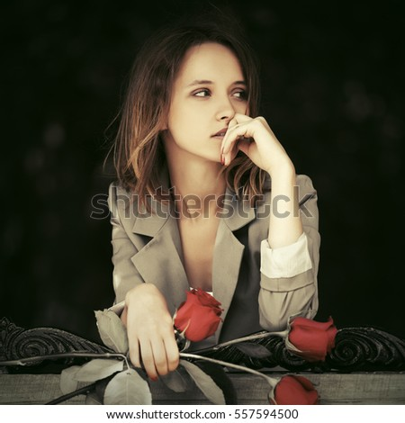 Sad young woman with red roses Stylish fashion model outdoor