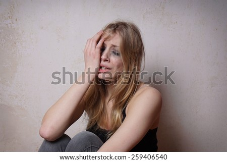 sad young woman with tear-stained face and smudgy makeup from crying     - stock photo