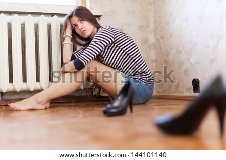 sadness girl sitting on the floor in the corner - stock photo