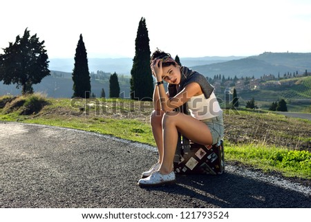 Sadness hitchhiker young girl sits on the suitcase on a rural road. Tuscan, Italy - stock photo