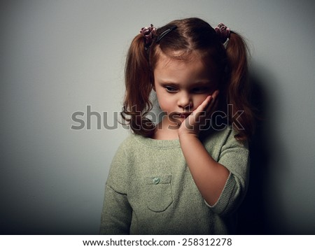 Sadness kid girl looking unhappy. Closeup portrait on dark background with shadows - stock photo
