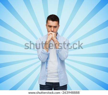 sadness, problem, sorrow and people concept - unhappy man thinking over blue burst rays background - stock photo