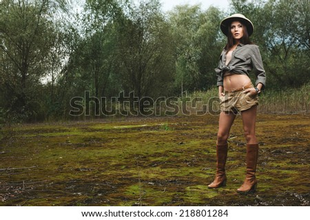 safari woman in swamp wearing safari hat standing on moss - stock photo