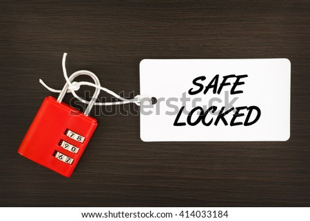 Safe Locked written on label tag with combination number padlock on wooden background - stock photo