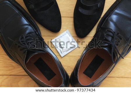 Safe sex Man shoes and woman heels with condom in the middle. A concept of having safe sex. - stock photo