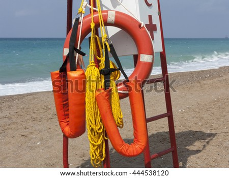Safe water support aid circle with rope. Rescue red life buoy on wooden background of ship or boat. Helpful object. - stock photo