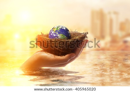 Safe world concept . Two Hand holding the world ball on bird nest in water on Blur City background.Copy Space on horizontal sheet.Elements of this image furnished by NASA. Earth Day - stock photo