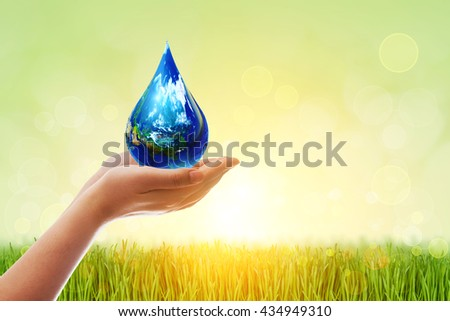 Safe world concept . Two Hands Wait for the world in water droplet shape on green bokeh background .Elements of this image furnished by NASA.United Nations Climate Change Conference - stock photo