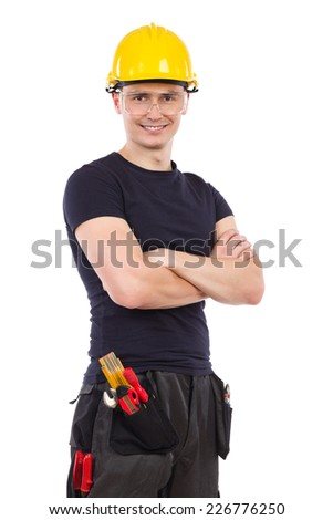 Safety at work. Construction worker wearing protective glasses and yellow hardhat posing with arm crossed. Three quarter length studio shot isolated on white.
