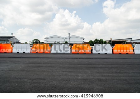 Safety Barrier Fence racing on asphalt road with blue sky - stock photo