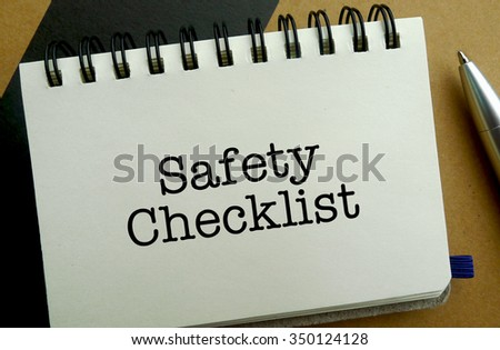 Safety checklist memo written on a notebook with pen - stock photo