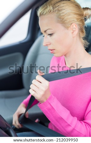 Safety first. Beautiful blonde caucasian lady fastening car seat belt. - stock photo