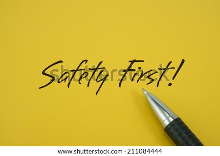 Safety First! note with pen on yellow background - stock photo