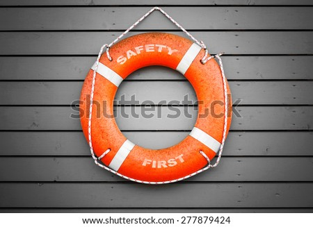 Safety first. Red lifebuoy with text label hanging on gray wooden wall of a port building - stock photo