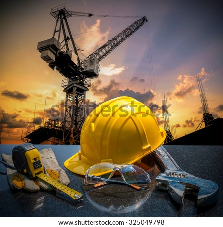 Safety gear kit and tools standing in front of construction site background concept - stock photo