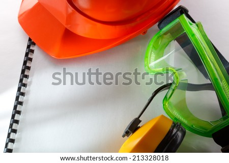 Safety goggles, earphones and red helmet - stock photo