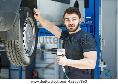 Safety guaranteed. Shot of a professional car mechanic smiling to the camera posing near a car he is working on holding an electric wrench