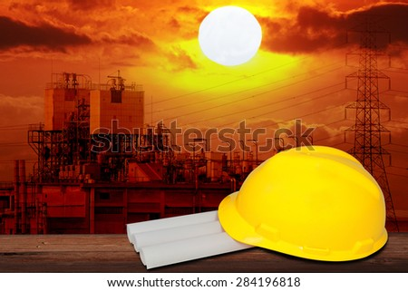 safety helmet and architect plant on wood table with industrial factory background. - stock photo