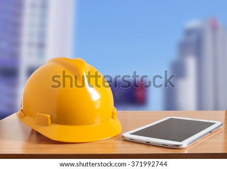 Safety helmet and tablet on wooden with construction site background - stock photo