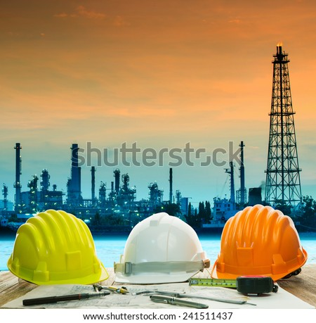 safety helmet on engineer working table against beautiful oil refinery in industry estate