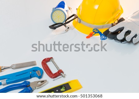 Safety helmet with other standard safety tools on white background.