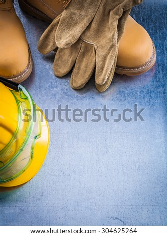Safety lace boots protective working gloves hard hat and transparent goggles on scratched metallic surface construction concept. - stock photo