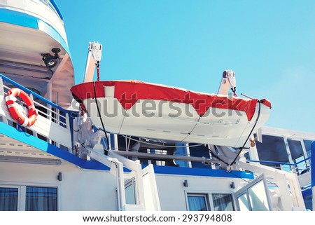 Safety lifeboat, small boat hanging on the deck of the cruise ship - stock photo