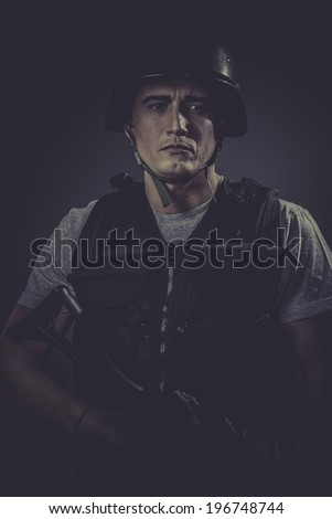 Safety, paintball sport player wearing protective helmet aiming pistol ,black armor and machine gun - stock photo