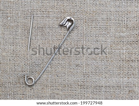 Safety pin on jute background. - stock photo