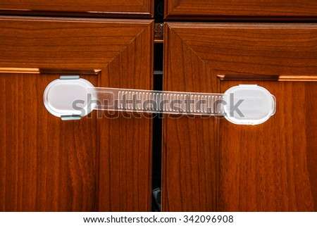 Safety plastic lock for kid protection on wardrobe - stock photo