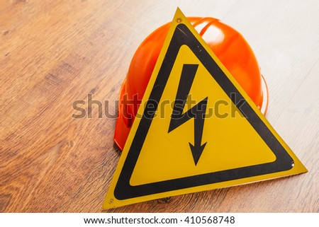 Safety  sign high voltage and red hard hat on a wooden background - stock photo