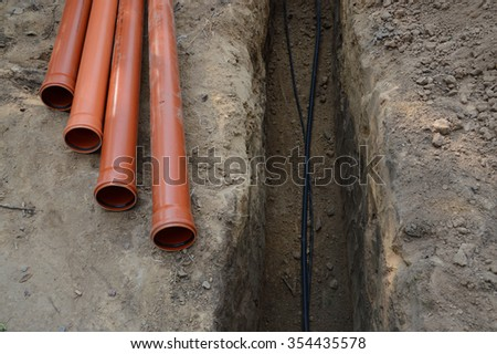 Safety supply to house new insulated internet, gas cord, red metal-plastic tap system construction lay in pit dug in garden. Top view with space for text on grey clay earth. Telecom service industry - stock photo