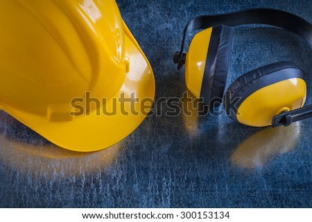 Safety yellow ear muffs and work helmet on scratched metallic background close up view construction concept.