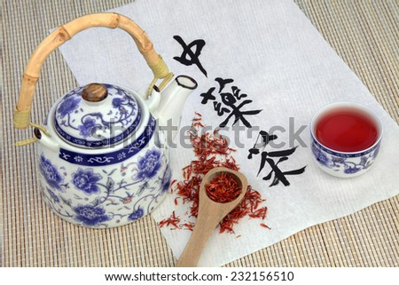 Safflower herb tea also used in chinese herbal medicine, with teapot, cup and calligraphy script on rice paper. Translation reads as chinese herbal tea. - stock photo