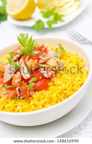 saffron rice with tuna, tomatoes, peppers and greens close-up, vertical - stock photo