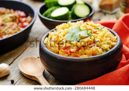 saffron rice with vegetables and cilantro on a dark wood background. the toning. selective focus  - stock photo