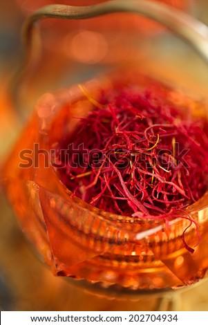 saffron spice in antique vintage glass bowl, closeup - stock photo