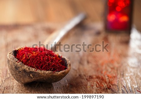 saffron spice in antique wooden spoon on old wood background, closeup - stock photo