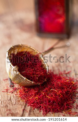 saffron spice in rustic sieve on old wooden background, closeup - stock photo