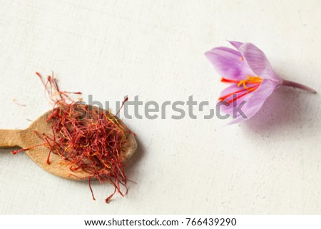 Saffron types in a spoon and saffron flower on a white background