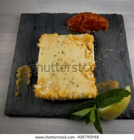 Saganaki. Traditional pan-fried Graviera cheese served with lemon marmalade  - stock photo