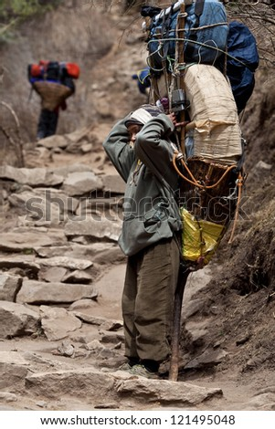 SAGARMATHA NATIONAL PARK, NEPAL - MARCH 06: Porters carry heavy load in the Himalaya, Nepal on March 06, 2010 in Sagarmatha National Park, Nepal