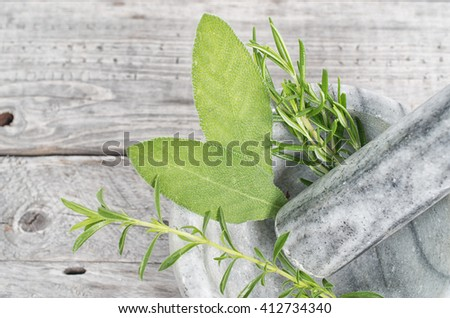 Sage and rosemary with mortar and pestle on wooden table
