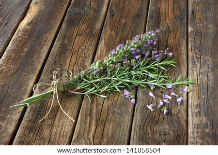 sage flowers and rosemary on wooden table - stock photo