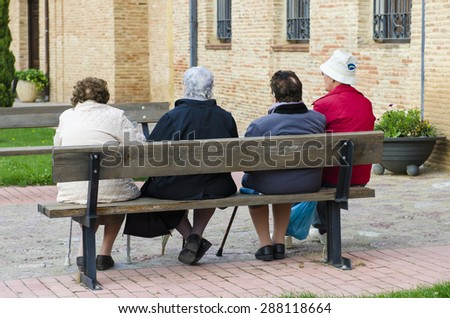 SAHAGUN, SPAIN - OCTOBER 11, 2014: Four elderly women chat, sitting on a bench in the historic town. - stock photo
