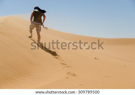 Sahara desert landscape with blue sky. Dunes background with man from behind walking - stock photo