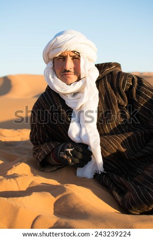 Sahara Desert MOROCCO DEC 31st 2014 : An unidentified camel-man sits on the sand dune in Sahara Desert while waiting for customers to see last sunset of the year - stock photo