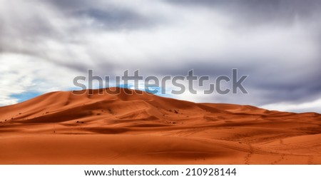 Sahara Desert sand dunes under gathering storm clouds. Copy space for text. Concepts: challenge, opportunity, silver lining, adventure - stock photo