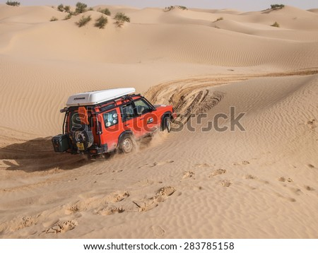 SAHARA DESERT, TUNISIA - OCTOBER 12 - 4X4 vehicle navigate the dunes of the Sahara as part of a guided tour on 12 October 2010.  North Africa is a popular destination for overland travel tours. - stock photo